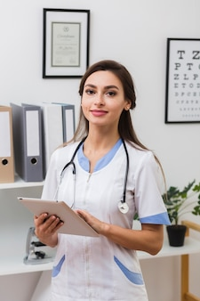 Улыбающиеся женщина-врач, держа в папку