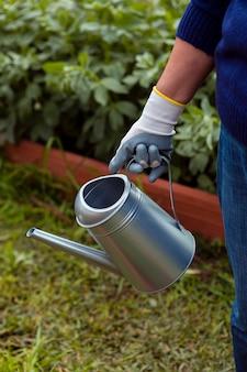 Крупный план садовника с разбрызгивателем