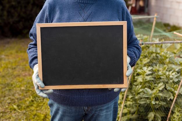 Садовник держит пустую доску