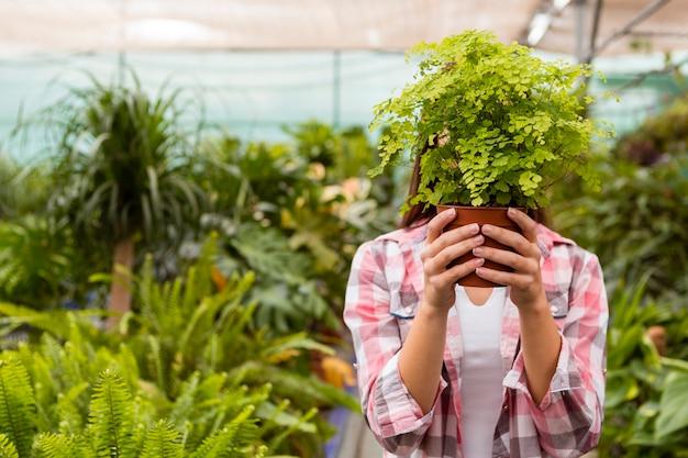 庭で頭を覆う植木鉢を保持している女性