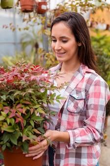 大きな植木鉢を保持している笑顔の女性の肖像画