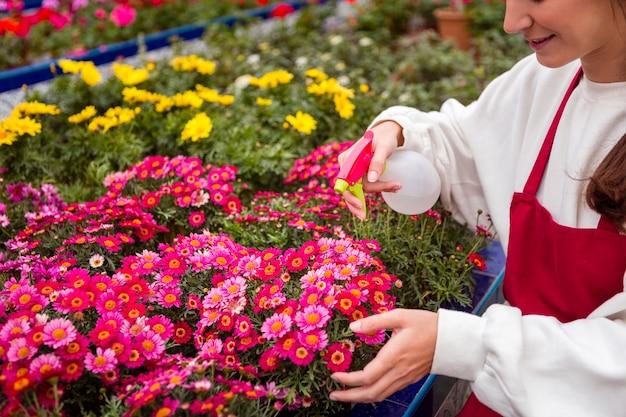 温室の花を吹きかけるクローズアップの女性