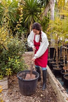 大きな植木鉢でシャベルをする女性