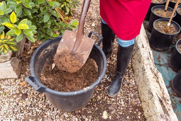 大きな植木鉢でシャベルで女性を閉じる