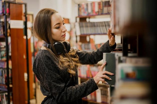 Наушники женщины нося вокруг шеи кладя книгу на полку