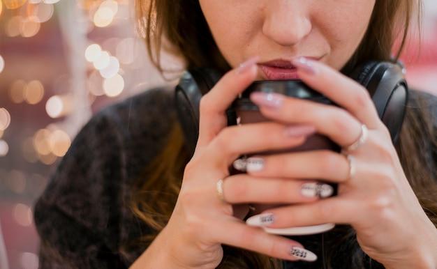 Наушники женщины конца-вверх нося выпивая из чашки около светов рождества