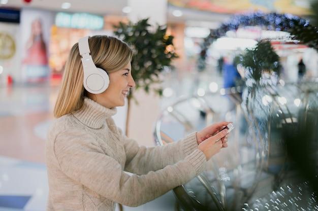 Наушники женщины нося и телефон держать в торговом центре