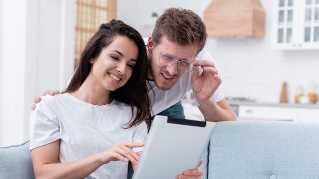彼女のボーイフレンドがタブレットで何かを示すガールフレンド