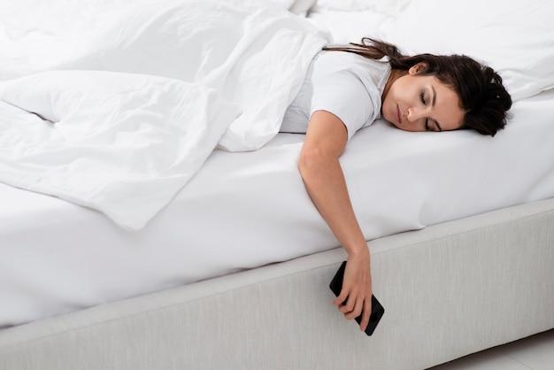 彼女の電話を押しながら寝ている女性