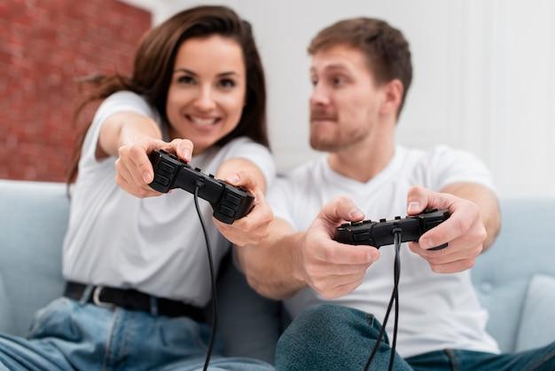 Вид спереди мужчина и женщина с удовольствием во время игры с контроллерами