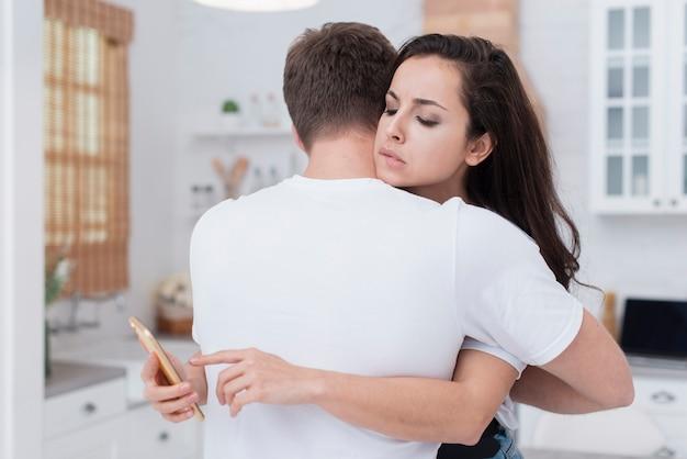 Пара обнимает, пока девушка смотрит на ее телефон