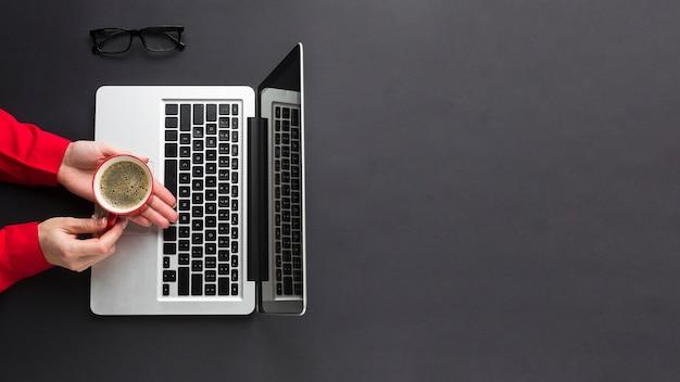 机の上のラップトップ上のコーヒーカップを持っている手の平面図
