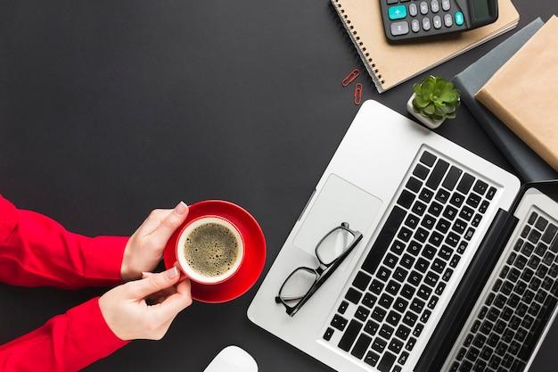 机の上のコーヒーカップを保持している手のトップビュー