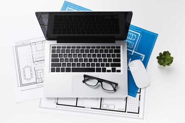 Вид сверху рабочего пространства с ноутбуком и чертежами