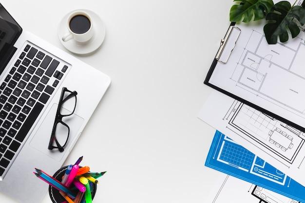 Вид сверху рабочего стола с ноутбуком и чертежи