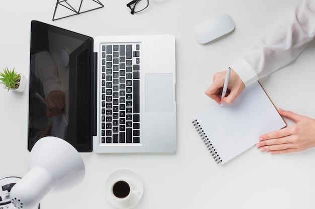 仕事机の上のノートパソコンとコーヒーカップのトップビュー