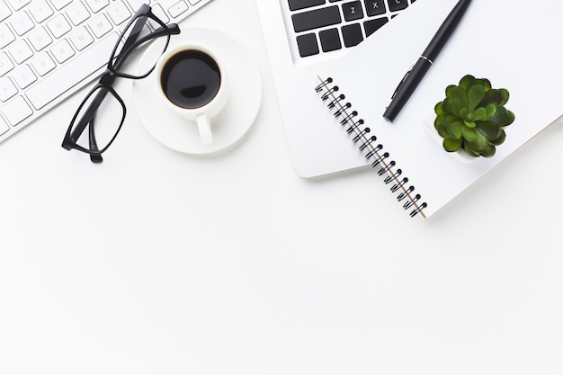 デスクトップ上のコーヒーカップとノートブックのフラットレイアウト