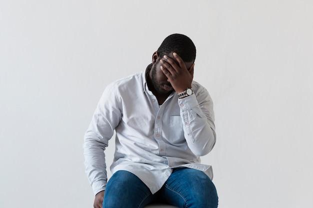 Вид спереди афро-американского человека, закрывающего лицо