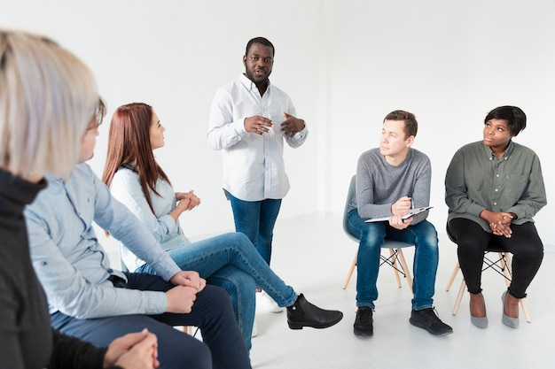 Афроамериканец разговаривает с пациентами реабилитационного центра
