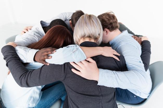 Люди обнимаются и собираются в круг
