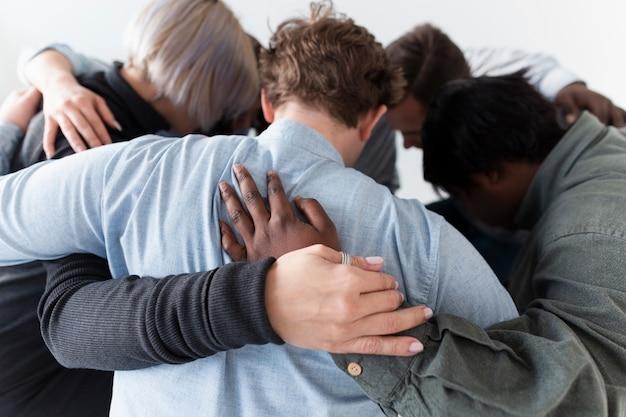 輪になって抱きしめる人々