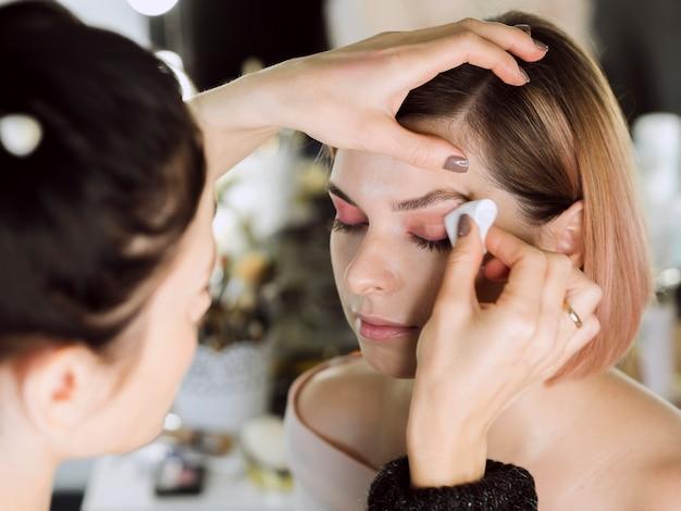 モデルからアイメイクを削除する女性