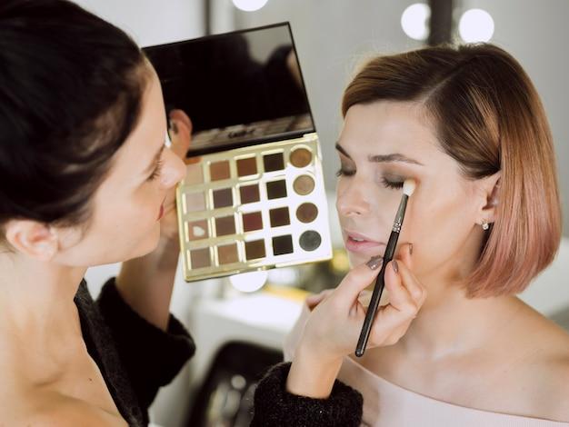 Художник наносит макияж по модели
