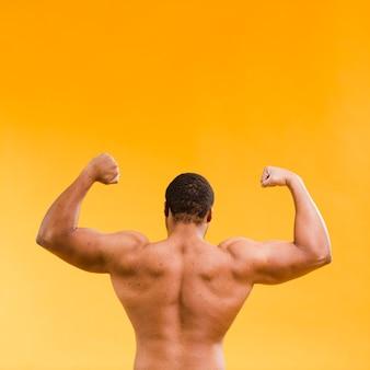背中の筋肉を示す運動の上半身裸の男