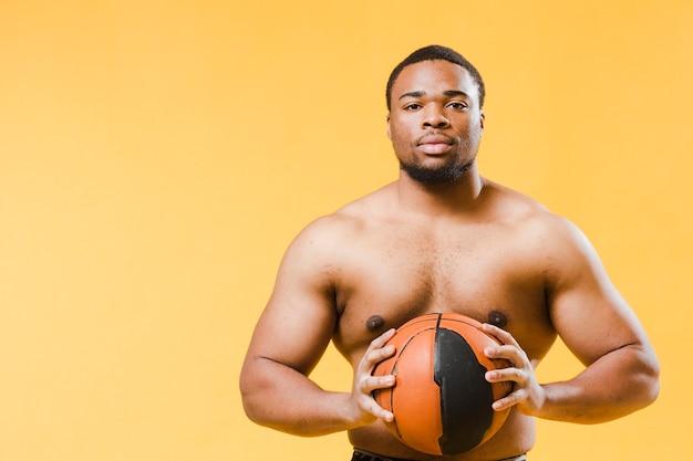 バストボールを保持している上半身裸の運動男