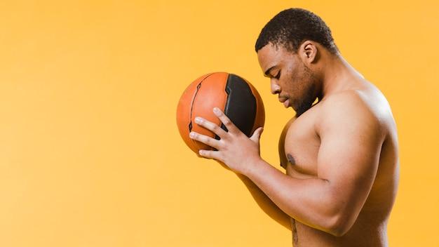 バスケットボールを保持している上半身裸の運動男の側面図