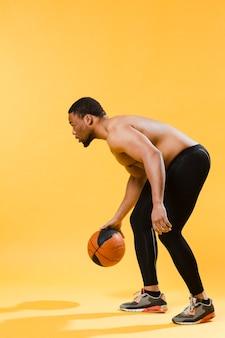 バスケットボールをしている上半身裸の運動男