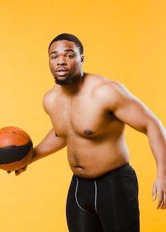 上半身裸のバスケットボールをする運動人
