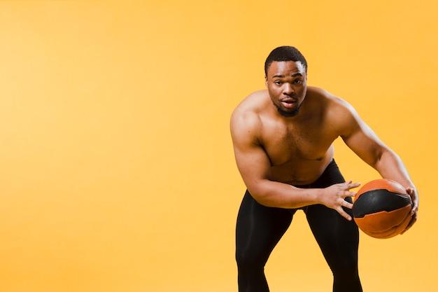 コピースペースで上半身裸のバスケットボールをする運動の男