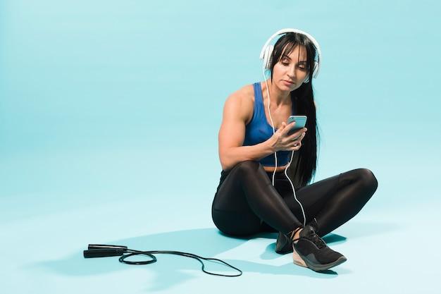 Женщина в спортивном наряде слушает музыку в наушниках со скакалкой