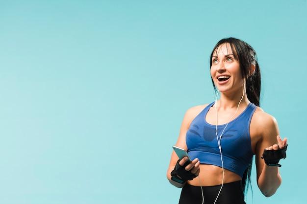 ヘッドフォンで音楽を楽しんでいるスマイリー運動女性