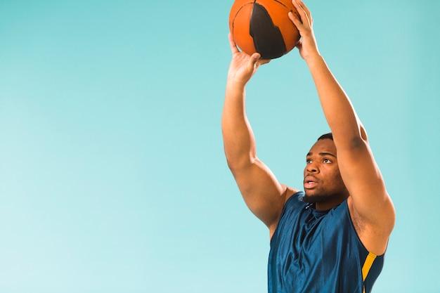 コピースペースでバスケットボールをする運動男性の側面図