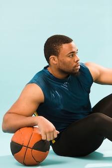 バスケットボールでポーズをとってジム服装で運動男
