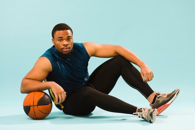バスケットボールでポーズをとって運動男の側面図