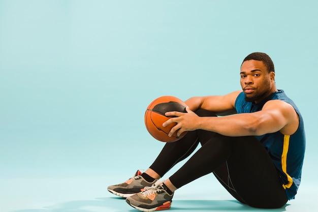 バスケットボールでポーズをとってジム服装で運動男の側面図