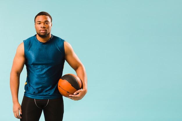 バスケットボールを保持している運動選手の男の正面図