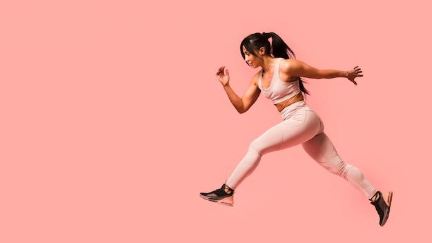 Вид сбоку спортивная женщина прыгает