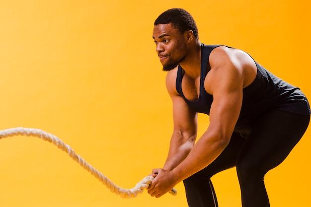 ロープとコピースペースを持つ運動男の側面図