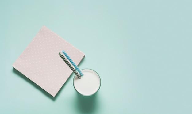 ピンクのナプキンの横にある牛乳のガラス
