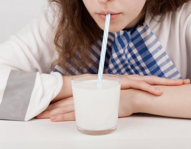 プラスチックストローで牛乳を飲む女の子