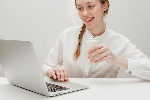 彼女のラップトップを見ながらミルクのガラスを保持している女の子