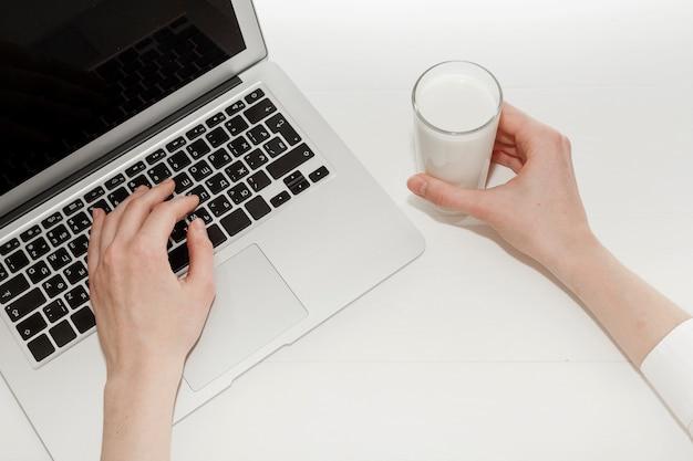 牛乳のガラスの横にあるラップトップで働いている人