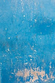 荒い木の表面の青いペンキ