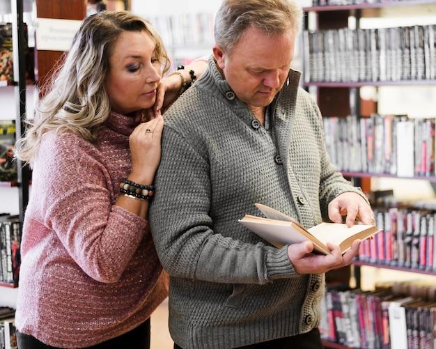 Женщина обнимает мужа в книжном магазине