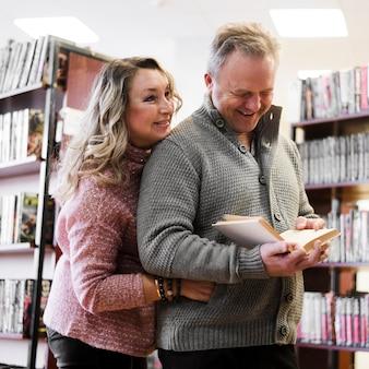 Счастливая пара старших в книжном магазине