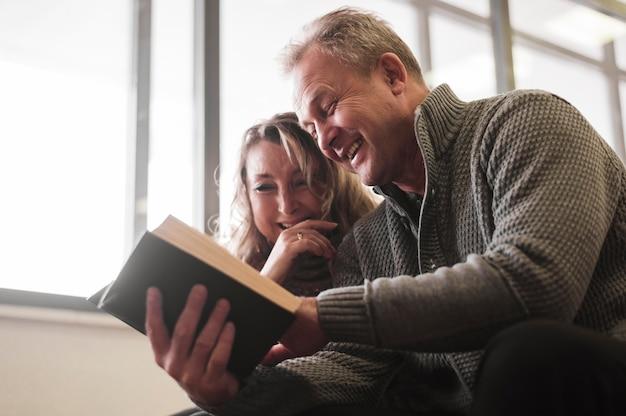 本で笑っている年配のカップル